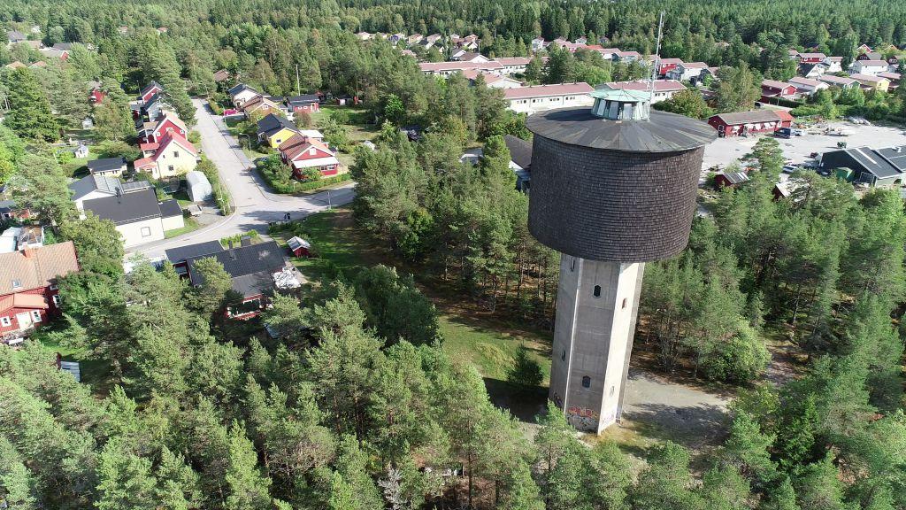 Bild på vattentorn i persktiv med skog och villaområde i bakgrunden.